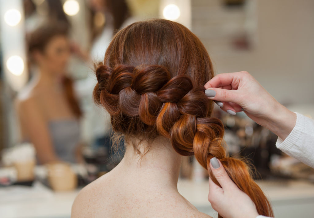 red-haired hairy girl, hairdresser weaves a French braid