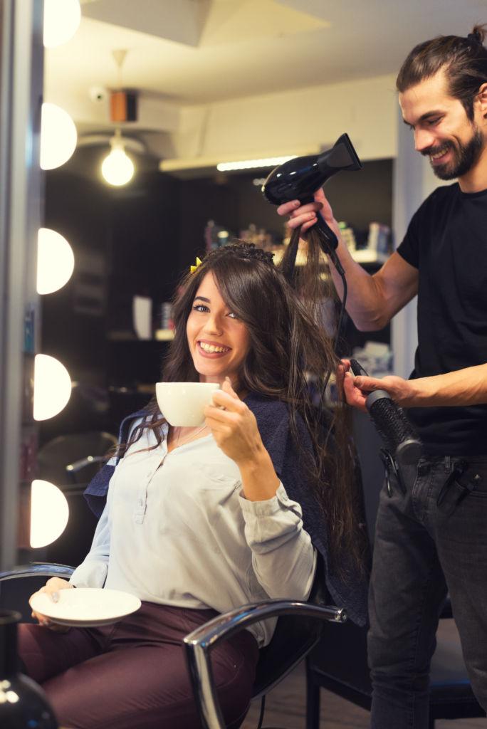 Woman drinking coffee in hair salon