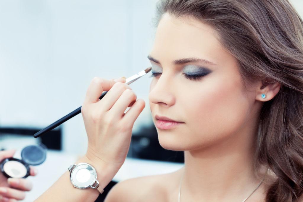Woman having eye shadow applied