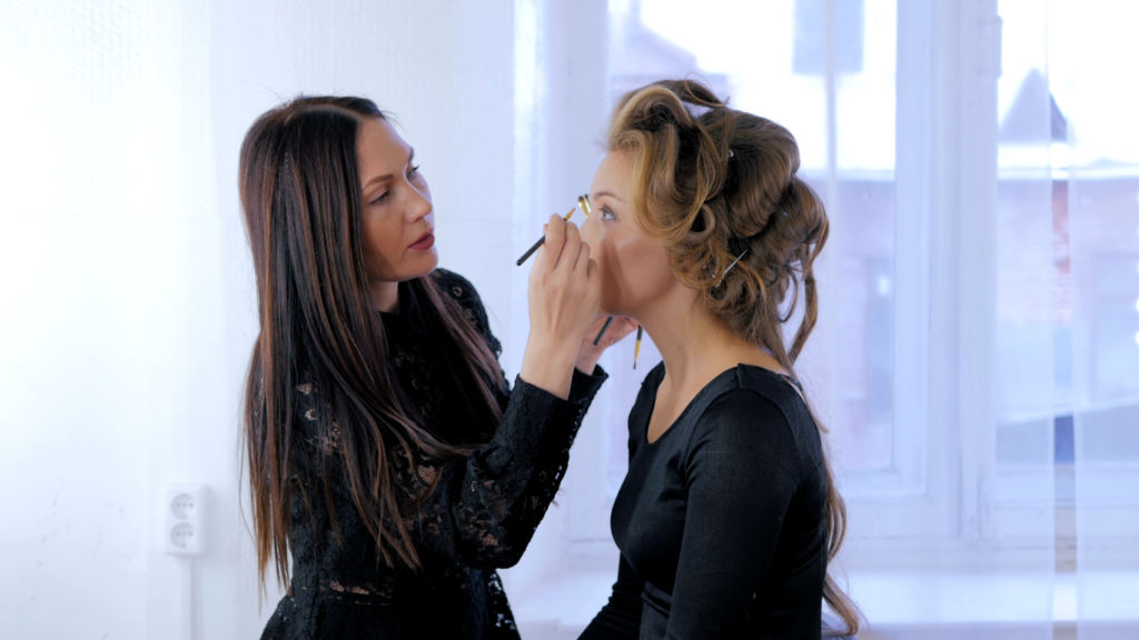 Professional make-up artist applying eyeliner around the entire eye of model
