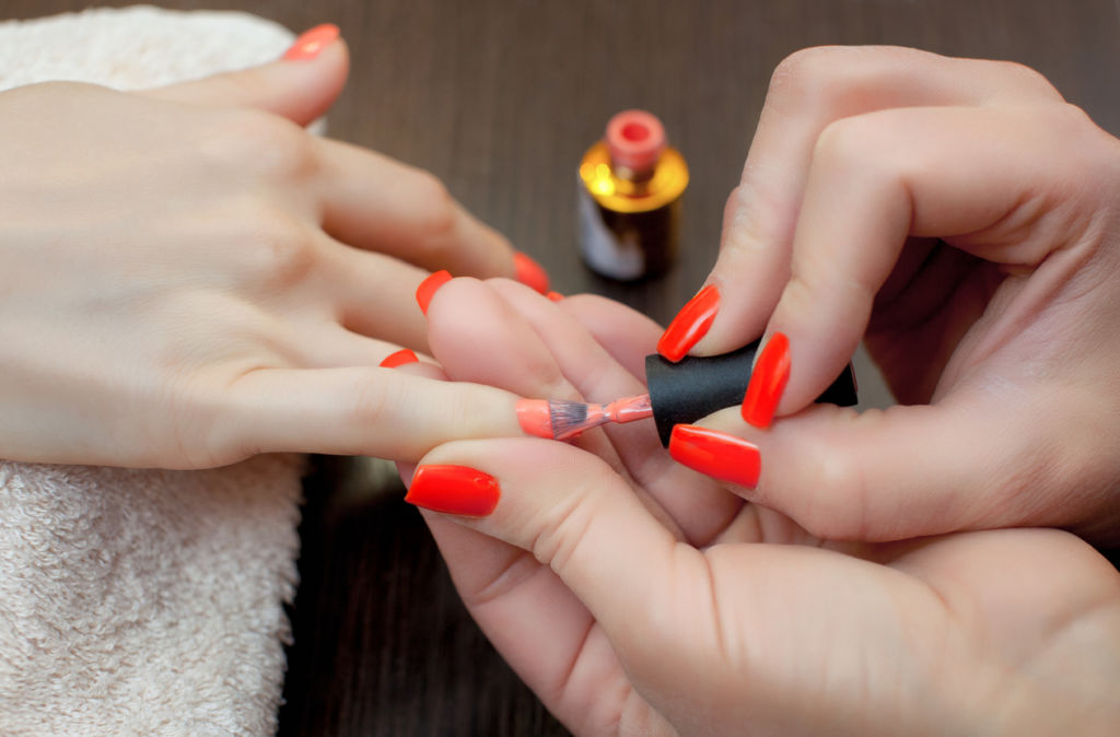 The master of the manicure paints nails with nail polish during the procedure of nail extensions with gel in the beauty salon. Professional care for hands.