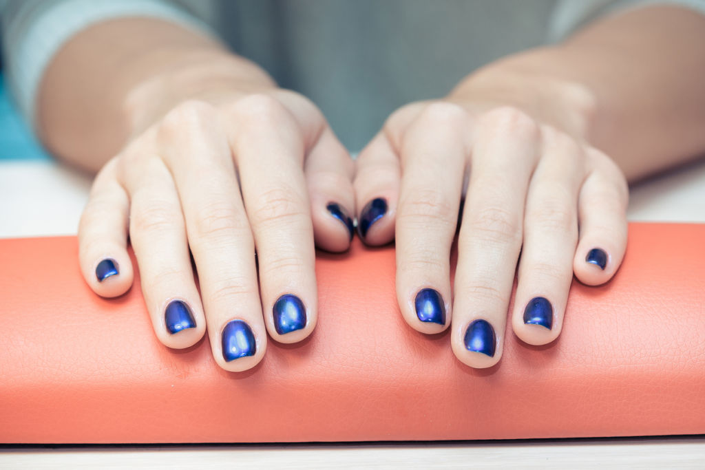 female hands with  blue nail Polish, close-up