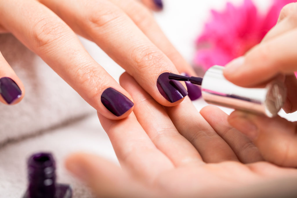 Woman having a nail manicure in  beauty salon