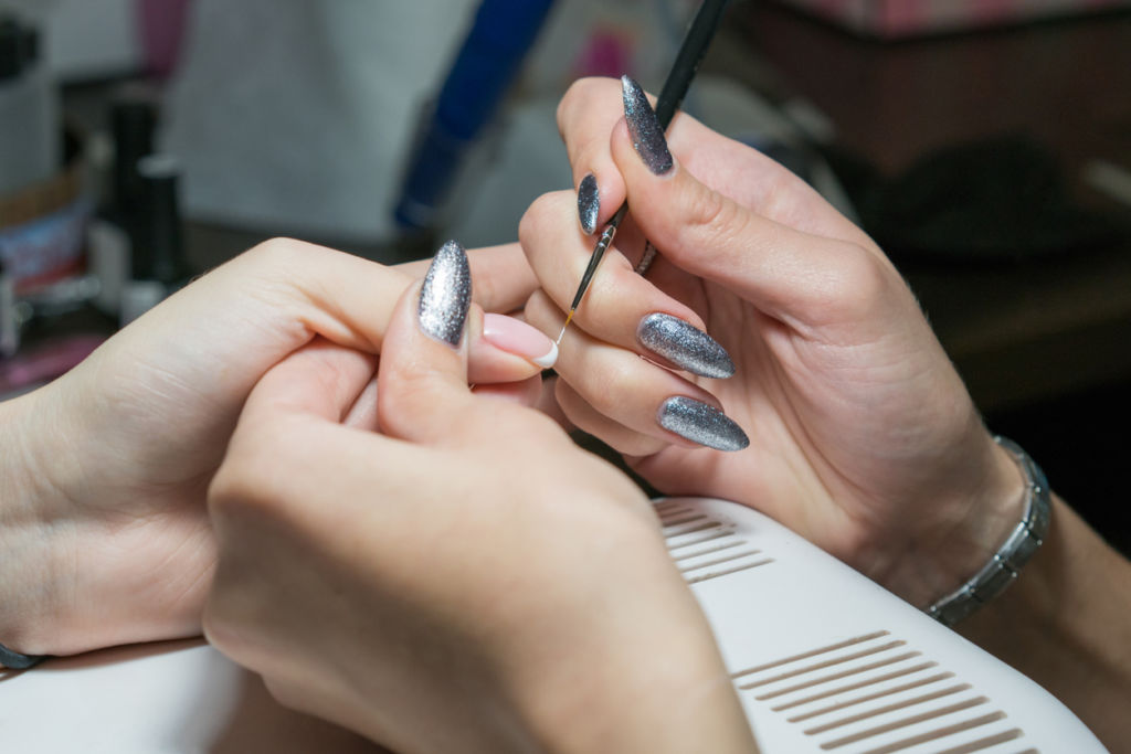 girl manicurist paints nails. Makes French manicure
